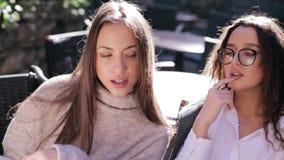 Deux jeunes belles femmes regardant le menu en restaurant, pages de rotation et choisissant des plats pour le petit d?jeuner clips vidéos