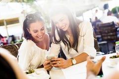 Deux jeunes belles femmes riant et souriant tout en à l'aide du téléphone Image libre de droits