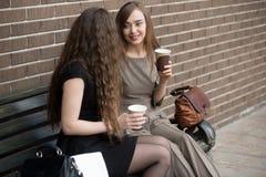 Deux jeunes belles femmes tenant les tasses de papier de café et de chatt Photographie stock libre de droits