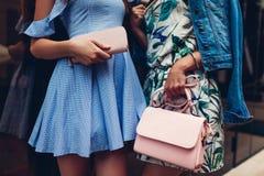Deux jeunes belles femmes utilisant les vêtements et les accessoires élégants Filles tenant la bourse et le sac à main Équipement photographie stock libre de droits