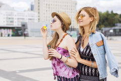 Deux jeunes belles filles blondes de hippie le jour d'été ayant le fu Image stock
