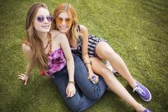 Deux jeunes belles filles blondes de hippie le jour d'été ayant le fu Photos stock