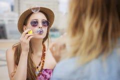 Deux jeunes belles filles blondes de hippie le jour d'été ayant le fu Image libre de droits