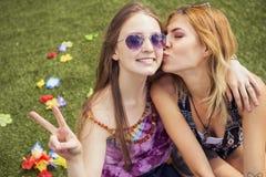 Deux jeunes belles filles blondes de hippie le jour d'été ayant le fu Photo stock