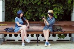 Deux jeunes belles filles dans des robes et des chapeaux de jeans s'asseyent sur un banc en parc sur un fond des murs de plante v Images stock