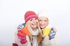 Deux jeunes belles filles de l'hiver avec la cuvette de thé Photos stock