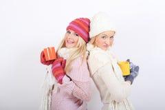 Deux jeunes belles filles de l'hiver avec la cuvette de thé Photos libres de droits