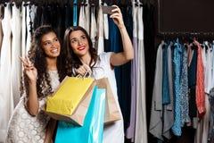 Deux jeunes belles filles faisant le selfie dans le centre commercial Images stock