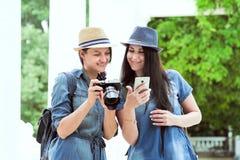 Deux jeunes belles filles marchent le long d'un parc vert avec les colonnes blanches Jour, le soleil Voyageurs, touristes, rire photos stock
