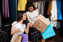 Deux jeunes belles filles regardant des achats dans le centre commercial Image stock