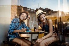 Deux jeunes belles filles souriant, riant, se reposant en café Tiré de l'extérieur Photographie stock