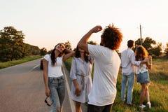 Deux jeunes brunes causant avec le jeune homme bouclé et rire extérieur un jour chaud photo libre de droits
