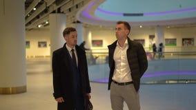 Deux jeunes businessmans attrayants dans des chemises blanches se tenant au centre commercial, discutent de nouvelles idées, réso banque de vidéos