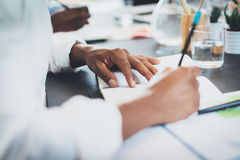 Deux jeunes collègues travaillant ensemble dans un bureau moderne et faisant des notes sur des documents Plan rapproché de stylo  Images stock