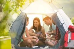 Deux jeunes couples ayant l'amusement sur des vacances en camping Photographie stock