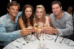 Deux jeunes couples dans le restaurant Image libre de droits