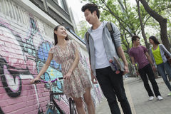 Deux jeunes couples descendant la rue par un mur avec le graffiti, souriant et flirtant les uns avec les autres Image libre de droits