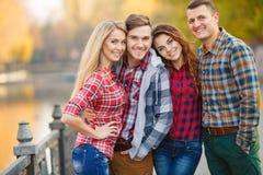 Deux jeunes couples passent le temps en parc Image libre de droits