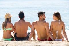 Deux jeunes couples sur la plage de sable Images stock