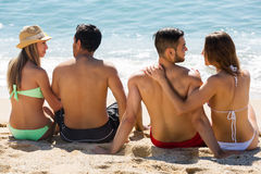 Deux jeunes couples sur la plage de sable Photographie stock libre de droits