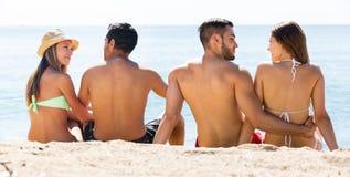 Deux jeunes couples sur la plage de sable Image stock