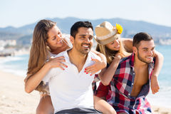 Deux jeunes couples sur la plage de sable Photos libres de droits