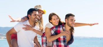 Deux jeunes couples sur la plage de sable Photo stock