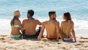 Deux jeunes couples sur la plage de sable Images libres de droits