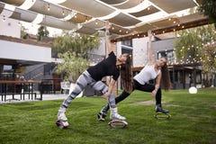Deux jeunes dames, 20-29 années, faisant un certain genre d'exercice dans des bottes de saut, images stock