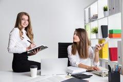 Deux jeunes dames d'affaires sur le lieu de travail dans le bureau blanc Image libre de droits
