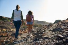 Deux jeunes dames flânant vers le haut de la colline Photo stock