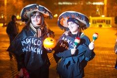 Deux jeunes dames habillées dans le chant de fête de costumes photographie stock libre de droits