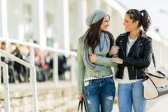 Deux jeunes dames marchant et faisant des emplettes heureusement tout en regardant e Photographie stock libre de droits