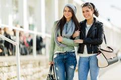 Deux jeunes dames marchant et faisant des emplettes heureusement un jour ensoleillé Photos stock
