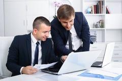 Deux jeunes directeurs dans le bureau images stock
