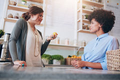 Deux jeunes employés féminins se tenant derrière le compteur de bar à jus Images libres de droits