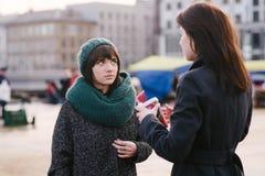 Deux jeunes et belles filles sont très élégants habillé, parlent le milieu de la ville Photos stock