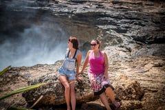 Deux jeunes et femmes sexy sur les roches près de l'océan sauvage Tempête, vagues énormes venant et éclaboussant Île tropicale Nu Image stock