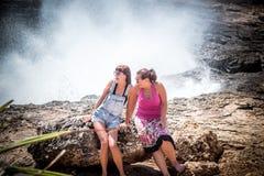 Deux jeunes et femmes sexy sur les roches près de l'océan sauvage Tempête, vagues énormes venant et éclaboussant Île tropicale Nu Photos libres de droits