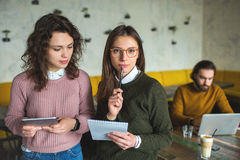 Deux jeunes femelles avec le smartphone et le comprimé en café Photographie stock libre de droits