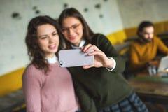 Deux jeunes femelles de sourire prenant le selfie en café Image libre de droits