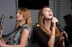 Deux jeunes femelles signent la chanson photographie stock libre de droits