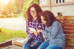 Deux jeunes femmes à l'aide de la tablette dehors Photographie stock