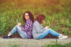 Deux jeunes femmes à l'aide de la tablette dehors Photos stock