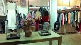 Deux jeunes femmes à la mode choisissent des manteaux d'automne et d'hiver dans un magasin moderne banque de vidéos