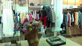 Deux jeunes femmes à la mode choisissent des vêtements dans un magasin d'habillement à la mode banque de vidéos