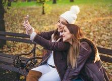 Deux jeunes femmes élégantes prenant un selfie Photos stock