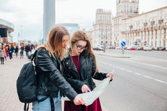 Deux jeunes femmes élégantes voyageant et regardant la carte dans la ville Image stock