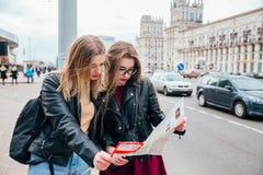 Deux jeunes femmes élégantes voyageant et regardant la carte dans la ville Photographie stock libre de droits