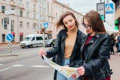 Deux jeunes femmes élégantes voyageant et regardant la carte dans la ville Photo stock